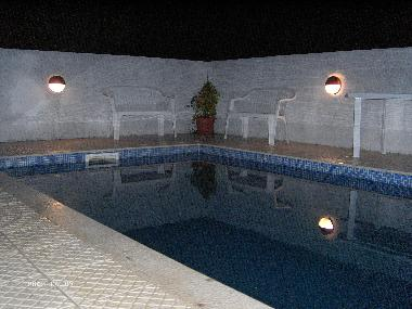 A view of the swimming pool at night with the lights on. shallow area approx 1 meter and at it's dee