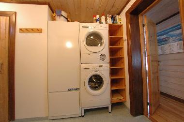 Washing machine & dryer along with generous storage bins for toilet bags and other toilet articles.