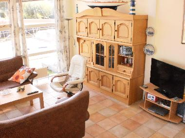 A tiled floor. 2 Sofa's, 2 relaxchairs, coffee table, sideboard, LED-TV, DVD etc.