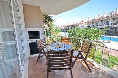 Terrace and BBQ of a one bedroom apartment. Direct access from the terrace to the pool area.